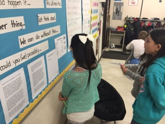 Students move to bulletin board for inspiration while writing.